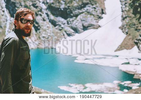 Man hiker traveling at blue lake in mountains Travel Lifestyle adventure concept summer vacations outdoor into the wild