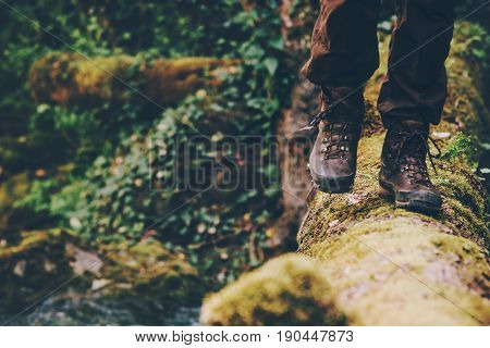 Man Traveler crossing over river on woods outdoor in wild forest Lifestyle Travel extreme survival concept summer adventure vacations
