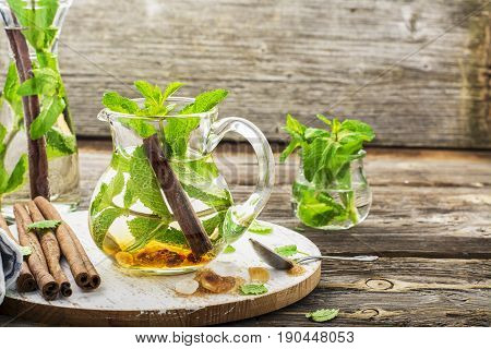 Cold refreshing Moroccan tea with cinnamon and mint in a tall decanter on a simple wooden background with a brown sugar caramel. Selective focus