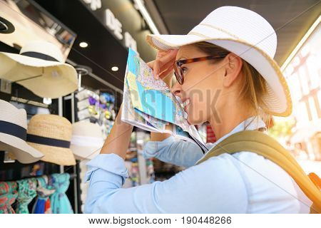 Portrait of beautiful woman trying summer hat on