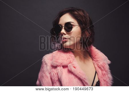 Young woman puffing a smoke with her nose on the black background.