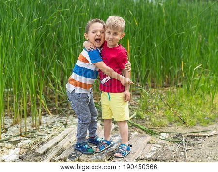 Two little boys friends hug each other in summer sunny day. Brother love. Concept friendship. Portrait of two boys brothers and best friends smiling. Friends hugging.