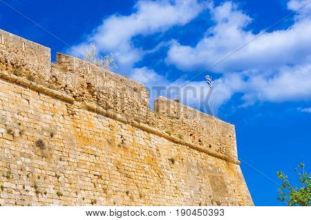 Greek flag flies on flagpole on tower of castle Fortezza - Venetian fortress on hill Paleokastro in resort Rethymno. Greek architecture on coast of Kolpos Almirou. Crete island Greece