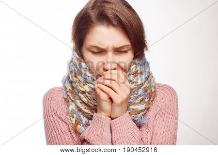 Young woman in scarf coughing and covering mouth with hands isolated on white background.