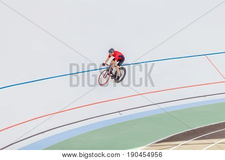 Active man on white velodrome outdoor. Sports man in a red T-shirt and a black bicycle.