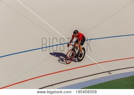 Racing cyclist on velodrome outdoor. Professional athlete in a red T-shirt and a black bicycle.