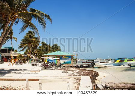 Caye Caulker Belize - February 28 2017: Beautiful tropical shore with water taxis on the island of Caye Caulker on the Barrier Reef in the Caribbean Sea