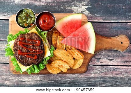 Picnic Scene With Open Hamburger, Potato Wedges And Watermelon On A Paddle Board Over Rustic Wood
