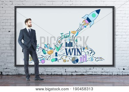 Young businessman in concrete interior looking at picture frame with rocket sketch. Entrepreneurship concept