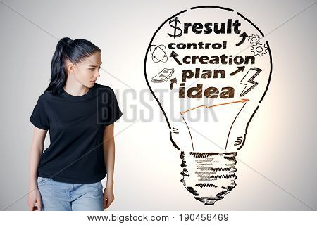 Pretty young girl on grey background looking at abstract lamp with text. Business process concept