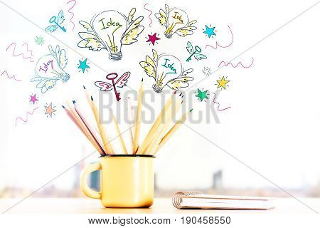Close up of iron mug with pencils and closed spiral notepad on blurry city background with coroful sketch. Inspire concept