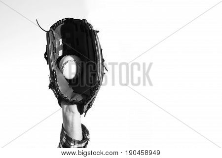 Hand in a baseball glove with a baseball ball on a white