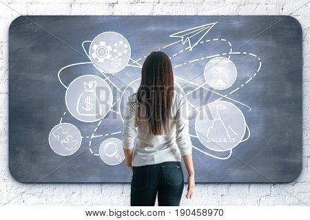 Back view of young woman drawing creative sketch on chalkboard. Leadership concept