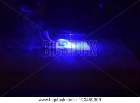 Laser engraving on wood macro. 3D printer laser beam burns the pattern close-up on a wooden board. Industrial Modern technological background. Laser blue 3d printer moves on a wooden surface