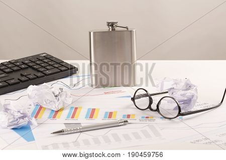 Desk with graphs keyboard glasses pen shredded papers and bottle of alcohol. Stress at work burn out alcoholism at work