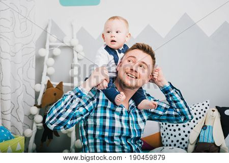 The Father Holds On Shoulders His Son