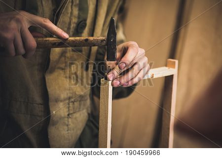 Man clogs a nail wooden frame for bees. Men's hands with long thin fingers hold wooden frame.