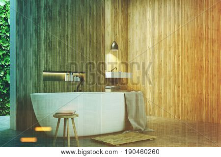 Eco bathroom corner with narrow windows green shrubbery is seen through them. There is a sink next to a white tub standing near a wooden wall. 3d rendering mock up toned image