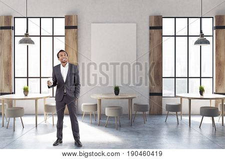 African American businessman in a modern cafe interior with concrete walls and floor wooden shutters at tall windows round tables and chairs and a vertical poster. 3d rendering mock up