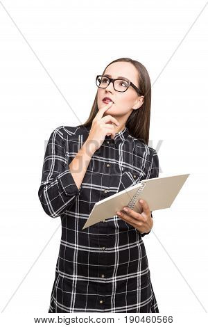 Isolated portrait of a beautiful geek girl with a copybook. She is wearing a checkered shirt and thinking about her academic career looking upwards.