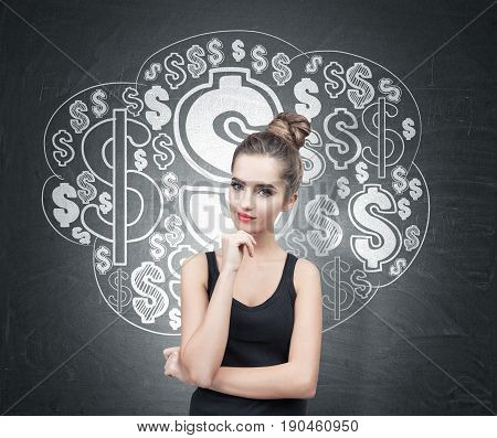 Portrait of a beautiful and pensive young woman wearing a black tank top. Her hair is in a bun. She is thinking and half smiling. Blackboard background with a dollar sign cloud sketch on it.