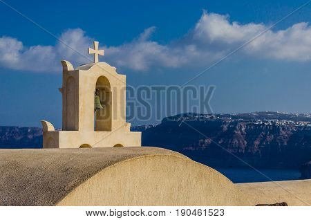 The cross that crowns the belfry of FIRA in Santorini - Greece