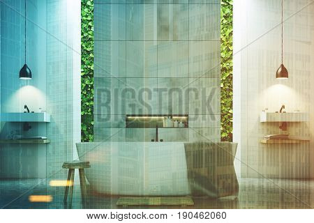 Eco bathroom interior with narrow windows green shrubbery is seen through them. There are two sinks by the sides of a white tub standing near a marble tile wall. 3d rendering mock up toned image