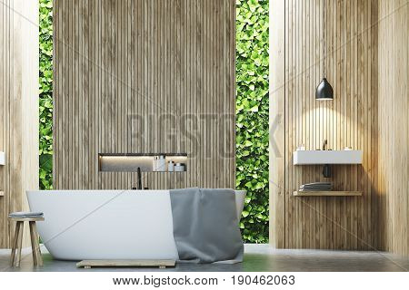 Eco bathroom interior with narrow windows green shrubbery is seen through them. There is a sink next to a white tub standing near a wooden wall. 3d rendering mock up