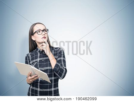 Portrait of a beautiful geek girl with a copybook. She is wearing a checkered shirt and thinking about her academic career looking upwards.