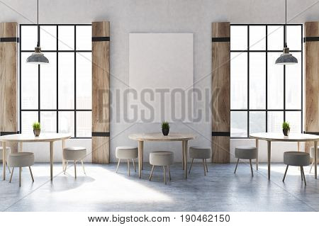 Modern cafe interior with concrete walls and floor wooden shutters at tall windows round tables and chairs and a vertical poster. 3d rendering mock up
