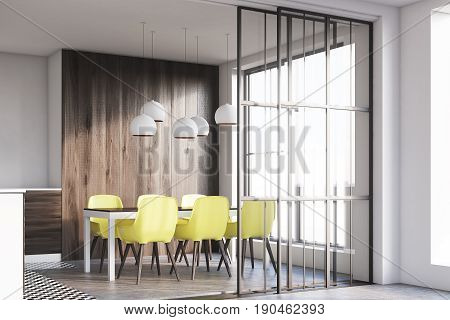 Side view of a dark wooden kitchen interior with white walls and wooden floor. Dining table with yellow chairs and countertops. 3d rendering mock up