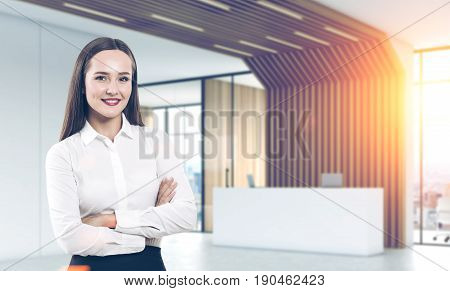 Young businesswoman in a white shirt is standing with crossed arms in an office lobby with a white reception counter two laptops on it and offices with glass walls. 3d rendering toned image