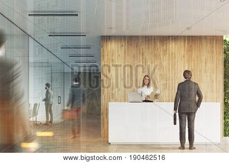 Rear view of businessmen near a white reception desk with two laptops standing on it in front of a wooden office wall. There are glass wall offices to the left. 3d rendering mock up toned image
