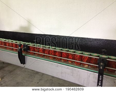 Working process of the production of Preserved red hot chili peppers on cannery. Pasteurization of cans. Movement on the conveyor.
