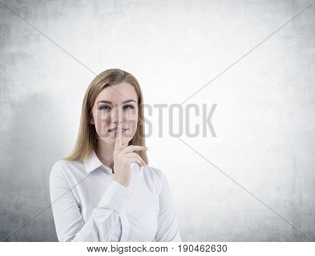 Portrait of a blond businesswoman wearing a white shirt and making a hush sign. Concept of conspiracy and keeping a secret. Concrete wall background. Mock up