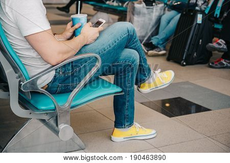 Young man using smartphone and seating on chair in waiting airport area, waiting for flight at airport