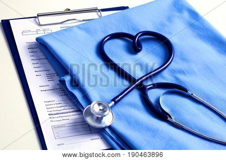 Medical stethoscope twisted in heart shape lying on patient medical history list and blue doctor uniform closeup.