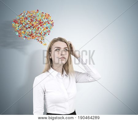 Front view of a confused blond businesswoman in a suit scratching her head and standing near a gray wall with a colorful speech bubble near her.