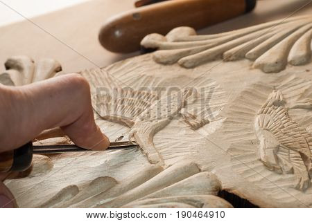 hands of the craftsman carve a bas-relief of wood, tools for wood carving, manual job