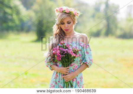Beautiful blonde girl holding bouquet of flowers at the countryside.