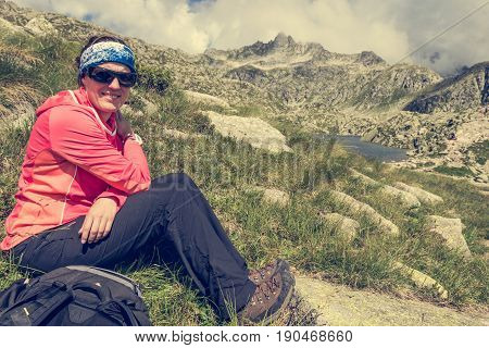 Female trekker resting on mountain meadow. Treking 5 Laghi above Madonna di Campiglio, Brenta in Italy.