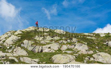 Trekker walking along a ridge. Trekking 5 Laghi trek in Brenta Dolomites.
