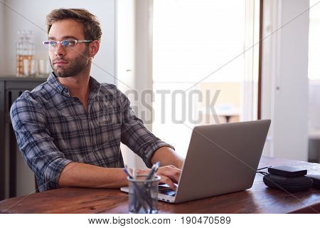 Successful young adult businessman looking back over his shoulder out of a whidow in thought with his hands still on the keyboard of his modern laptop at home.