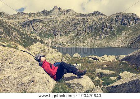 Tired trekker resting near mountain lake. Gelato Laghi, Brenta Dolomites in Italy.