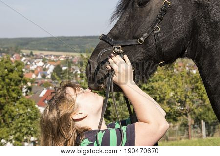 Beautiful young woman with her black horse outside Shot