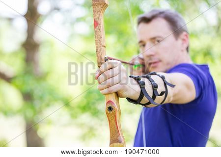 Bowman aiming arrow at target image with shallow depth of field left hand and bow in focus