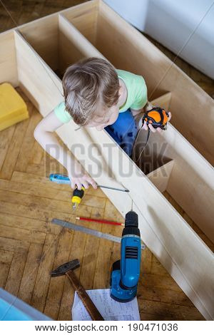 Cute young boy using screwdriver while sitting on floor at unfinished shelf unit or bookcase and holding tape measure in another hand
