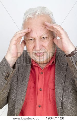 Skeptical senior male with hands on his forehead - on bright background