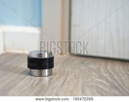 Metal modern door stopper on wooden floor.