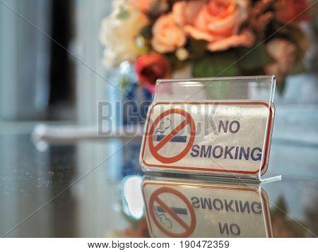 No smoking sign on wooden table. Warning symbol.